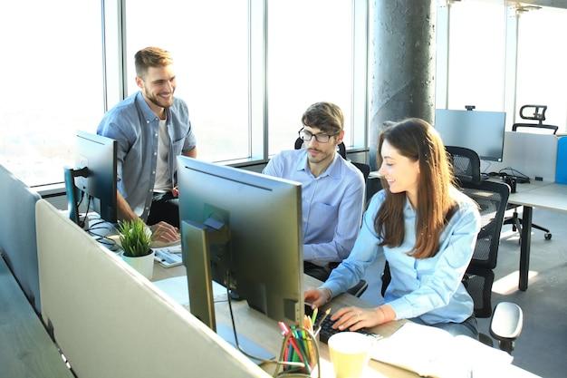 Jeunes collègues en tenue décontractée élégante travaillant tout en passant du temps au bureau.