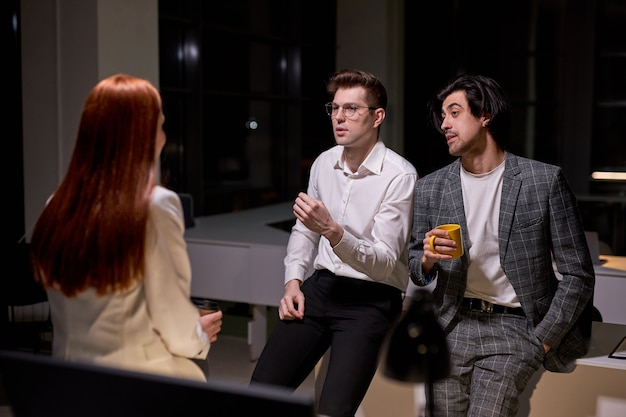 De jeunes collègues en tenue formelle discutent, prennent une pause tard dans la nuit dans la salle de réunion, sourient, discutent, partagent des idées, expliquent des plans. travail d'équipe, concept d'employés de bureau