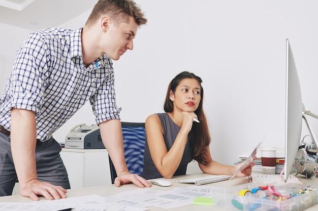 De jeunes concepteurs d'interface utilisateur sérieux discutant de croquis et de mises en page sur un écran d'ordinateur lorsqu'ils travaillent sur un nouveau projet