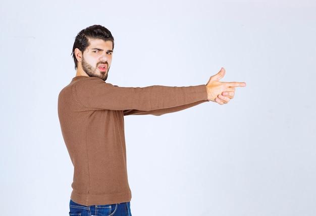 Jeunes confiants faisant un geste de tir comme agent secret.