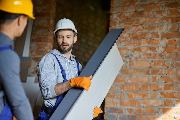 Jeunes constructeurs masculins confiants portant des casques semblant concentrés, tenant un goujon métallique pour les cloisons sèches