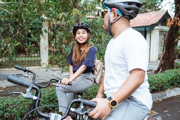 Les jeunes couples asiatiques portant des casques aiment faire du vélo ensemble