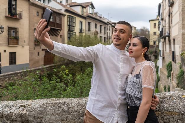 Les jeunes couples caucasiens amoureux prennent un selfie avec leur smartphone