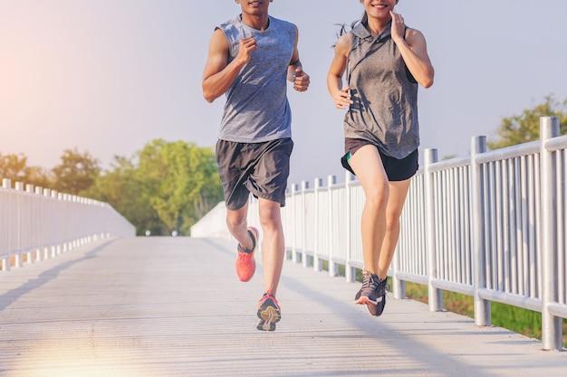 Jeunes couples en cours d'exécution sprint sur route. fit runner fitness runner pendant l'entraînement en plein air