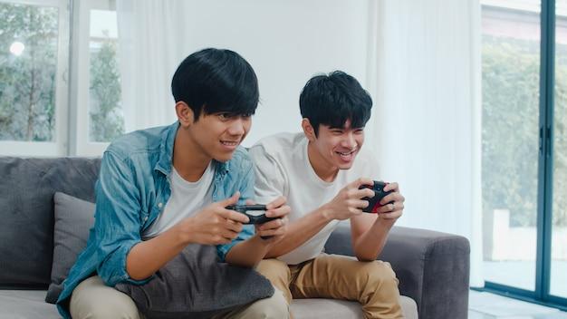 Jeunes couples homosexuels asiatiques jouent à la maison, adolescents lgbtq coréens utilisant un joystick ayant un moment de bonheur drôle ensemble sur un canapé dans le salon de la maison.