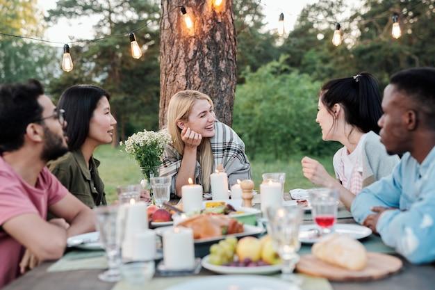 Jeunes couples joyeux assis par table de fête servie sous le pin, parler, rire et savourer des plats savoureux lors d'un dîner ou d'une fête en plein air