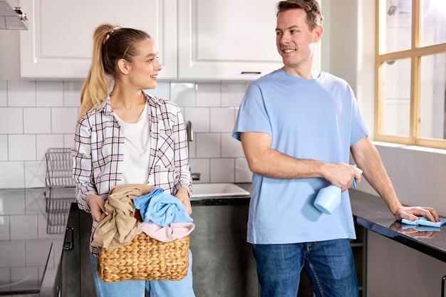 Jeunes couples mariés caucasiens à la cuisine de nettoyage à la maison