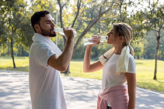 Jeunes couples qui boivent de l'eau après avoir fait de l'exercice dans le parc.