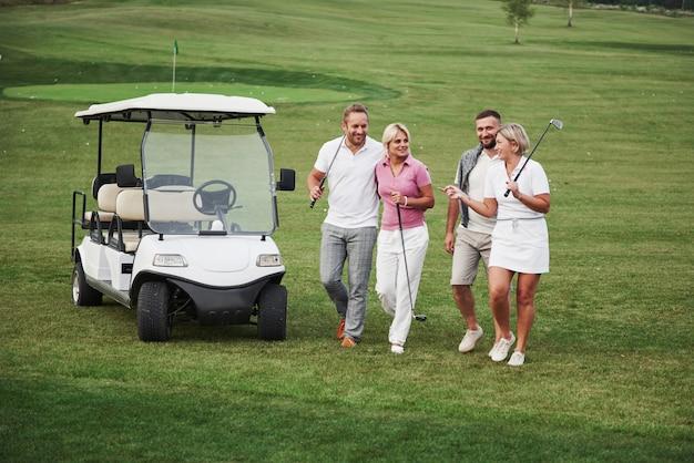 Jeunes couples s'apprêtent à jouer. un groupe d'amis souriants est venu au trou sur une voiturette de golf