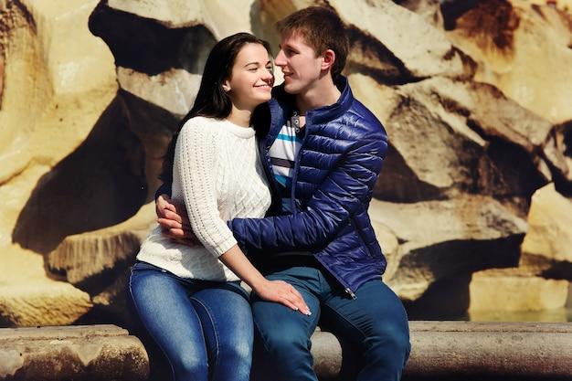 Les jeunes couples se câlinent avant le mur de pierre