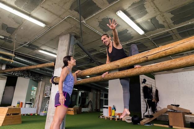 Les jeunes couples sportifs font la formation fonctionnelle au gymnase