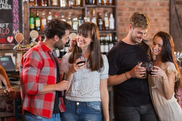 Jeunes couples tenant des boissons au bar