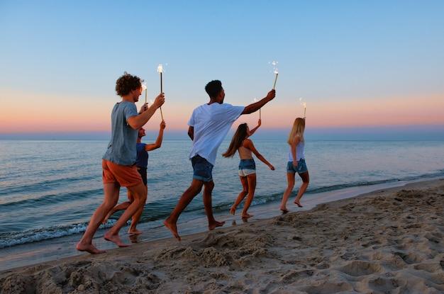 Les jeunes courent sur la plage avec des bougies scintillantes dans les mains