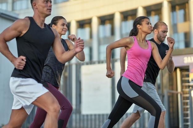 Jeunes coureurs multiraciaux en compétition sur la rue de la ville