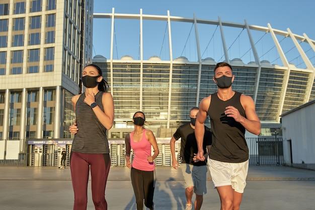 Jeunes coureurs multiraciaux en formation de masques de protection