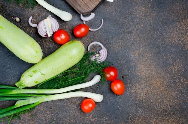 Jeunes courgettes, tomates, herbes et épices printanières sur une surface noire