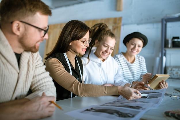 Jeunes créateurs discutant de croquis de mode assis près d'un bureau en studio et travaillant sur une nouvelle collection