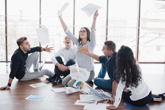 Jeunes créatifs dans un bureau moderne. groupe de jeunes gens d'affaires travaillent ensemble avec un ordinateur portable. pigistes assis par terre. réalisation d'entreprise de coopération. concept de travail d'équipe