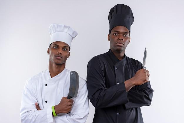 Les jeunes cuisiniers afro-américains confiants en uniforme de chef avec les bras croisés tenir les couteaux isolés sur fond blanc