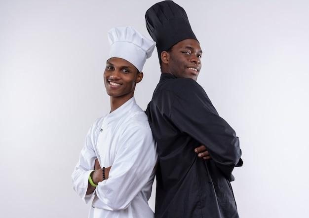 Les jeunes cuisiniers afro-américains souriants en uniforme de chef avec les bras croisés se tenir dos à dos isolé sur mur blanc