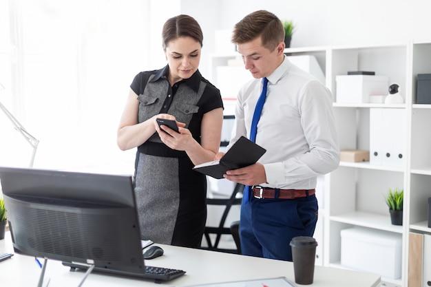 Les jeunes dans le bureau en regardant l'écran du téléphone.