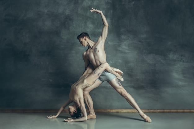 Les jeunes danseurs de ballet moderne avec des tatouages sur les corps posant sur fond gris studio