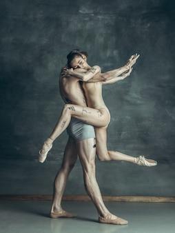 Jeunes danseurs de ballet modernes posant sur gris
