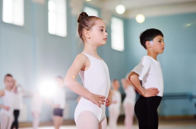 Jeunes danseurs dans le studio de ballet. les jeunes danseurs effectuent des exercices de gymnastique lors d'un échauffement en classe. sport, gymnastique, développement de l'enfant