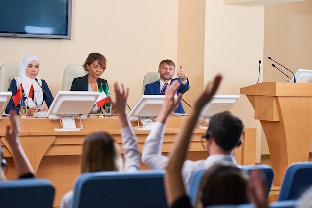 L'un des jeunes délégués confiants pointant le public pour question après son discours lors d'une conférence d'affaires