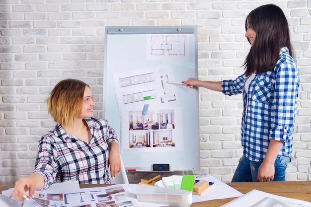Les jeunes designers d'intérieur travaillant en freelances développent un nouveau projet d'appartement en studio de design. deux femmes fille femme rencontre avec un bureau avec pin up esquisses dessins et projets de nouveau projet