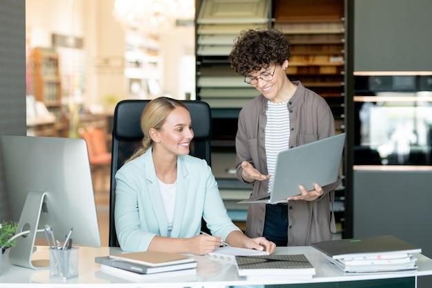 L'un des jeunes designers montrant à son collègue des idées en ligne sur un écran d'ordinateur portable lors d'une consultation au bureau