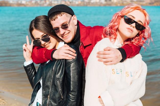 Jeunes détendus modernes embrassant et souriant au bord de la rivière