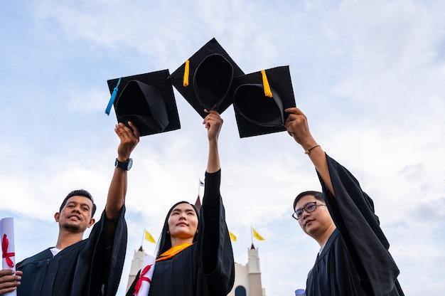 Jeunes diplômés asiatiques tenant des chapeaux de graduation