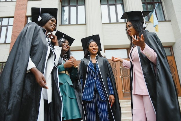 Jeunes diplômés debout devant le bâtiment de l'université le jour de la remise des diplômes