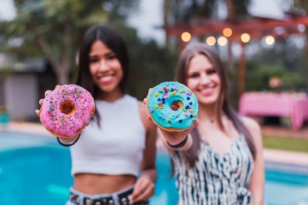 Jeunes drôles avec de délicieux beignets profitant de la journée à la piscine