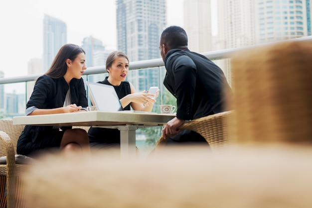 Les jeunes élégants ont une réunion d'affaires dans un restaurant à l'extérieur.
