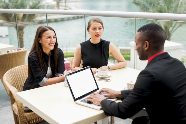 Les jeunes élégants ont une réunion d'affaires dans un restaurant près de la rivière.