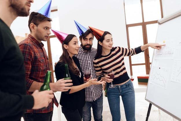 De jeunes employés de l'entreprise parlent près d'un tableau blanc
