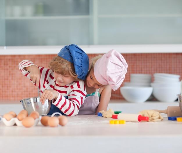 Jeunes enfants cuisinant à la maison