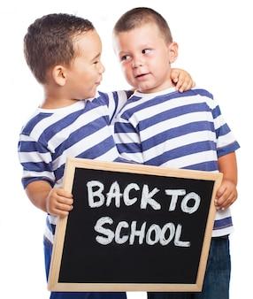 Les jeunes enfants embrassant un tableau noir avec le message «retour à l'école
