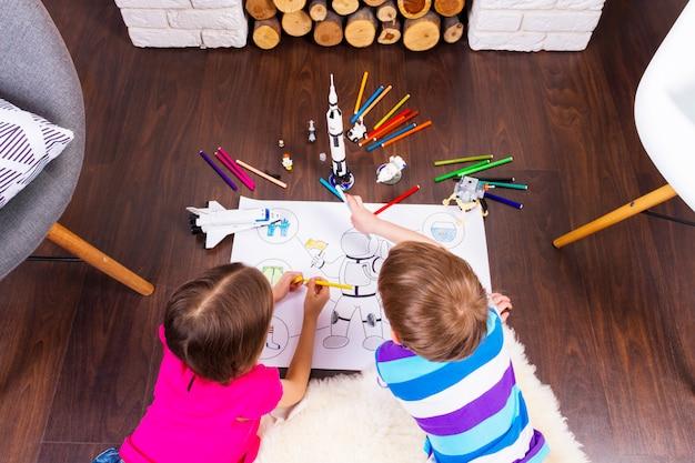 Jeunes enfants fille et garçon peignant le costume d'astronaute avec des stylos et rêvant de cosmos avec des jouets de constructeur de cosmonautes