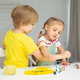 Jeunes enfants peignant à la maison