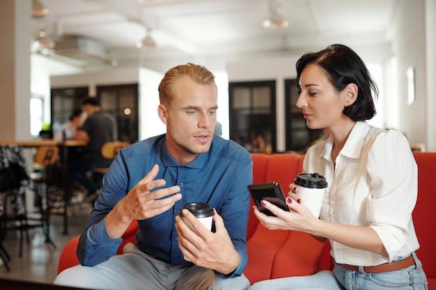 Jeunes entrepreneurs buvant du café au café et choisissant une nouvelle application mobile à utiliser pour la gestion de projet
