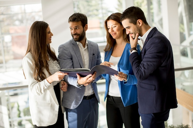 Jeunes entrepreneurs debout et analysant des documents