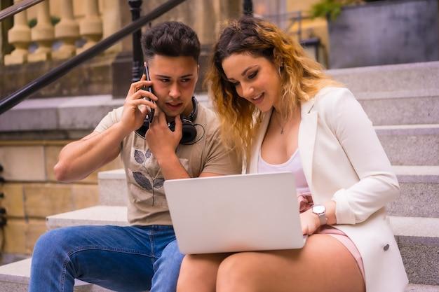 Jeunes entrepreneurs faisant un travail d'équipe. travailler sur internet avec l'ordinateur, garçon avec des écouteurs de musique et fille en costume blanc