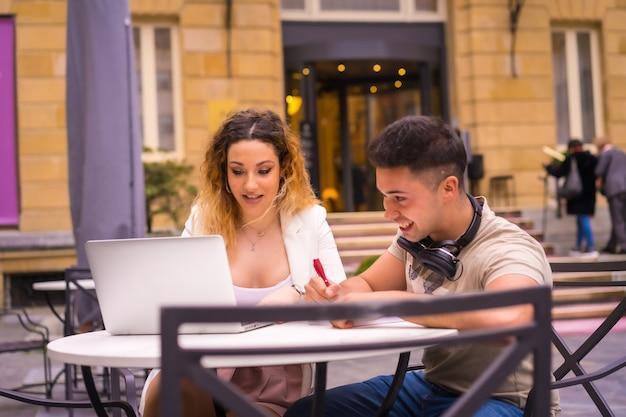 Jeunes entrepreneurs faisant un travail d'équipe. travailler sur internet avec l'ordinateur sur une terrasse d'un bar
