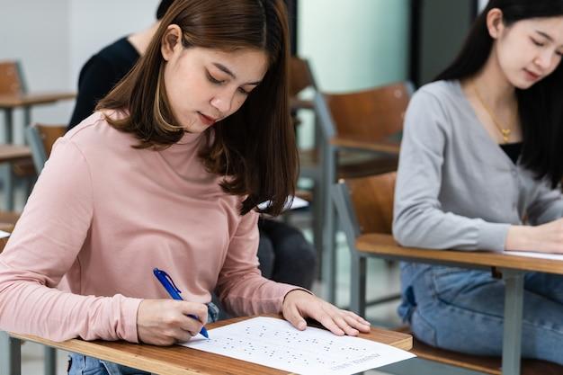 Les jeunes étudiantes universitaires se concentrent sur l'examen en classe. les étudiantes rédigent sérieusement l'exercice des examens en classe.