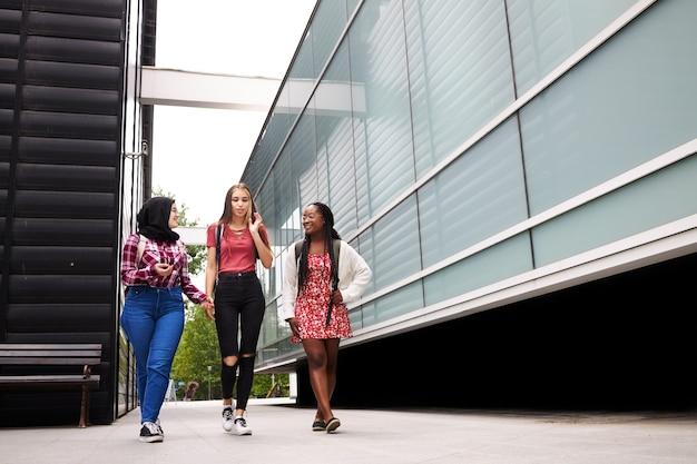 Jeunes étudiants discutant et traînant autour du campus universitaire