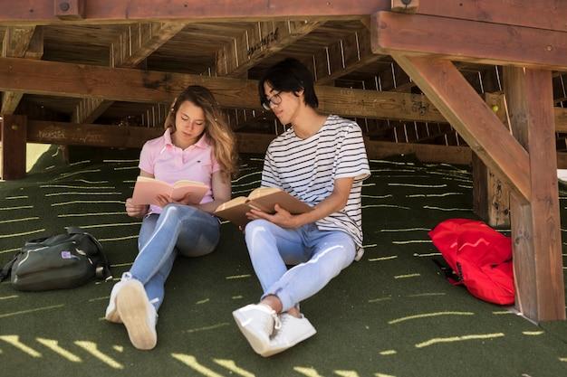 Jeunes étudiants divers avec bloc-notes sur l'herbe