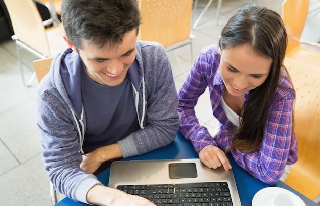 Jeunes étudiants effectuant une mission sur ordinateur portable ensemble